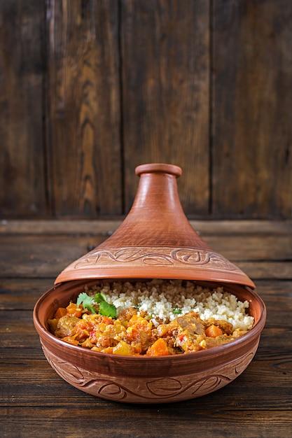 Tradycyjne potrawy tajine, kuskus i świeża sałatka na rustykalnym drewnianym stole. Premium Zdjęcia