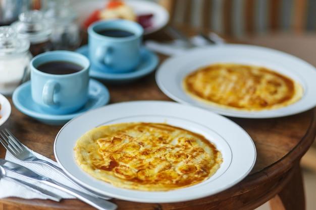 Tradycyjne śniadanie balinesse z dwoma niebieskimi filiżankami gorącego napoju na drewnianym stole. Premium Zdjęcia