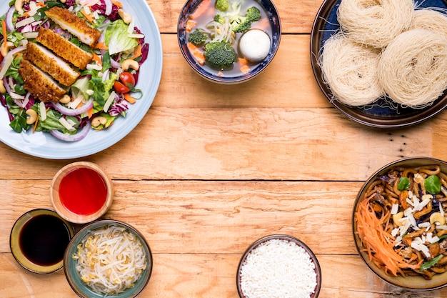 Tradycyjne tajskie jedzenie, w tym warzywa zupy smażone sałatki rybne i ryżowy wermiszel na drewnianym stole Darmowe Zdjęcia