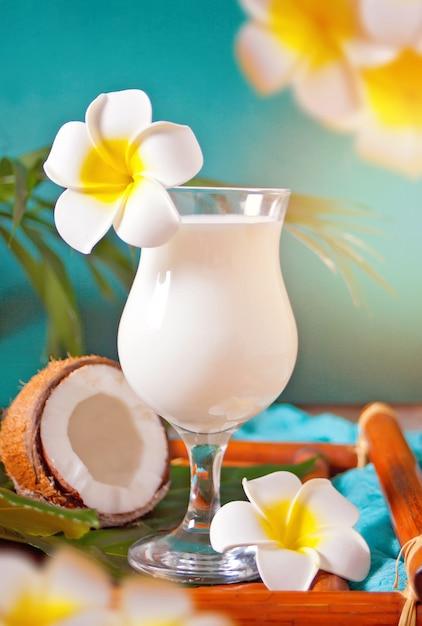 Tradycyjny Karaibski Egzotyczny Tropikalny Koktajl Pina Colada W Szklankach Z Kwiatami Plumeria Frangipani, Liściem Palmowym I Kokosem Na Powierzchni. Koncepcja Piknik Na Tropikalnej Plaży. Premium Zdjęcia