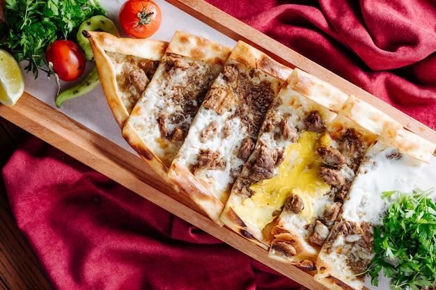 Tradycyjny Turecki Lahmacun Z Farszem Mięsno-serowym Podawany Na Drewnianym Talerzu. Darmowe Zdjęcia