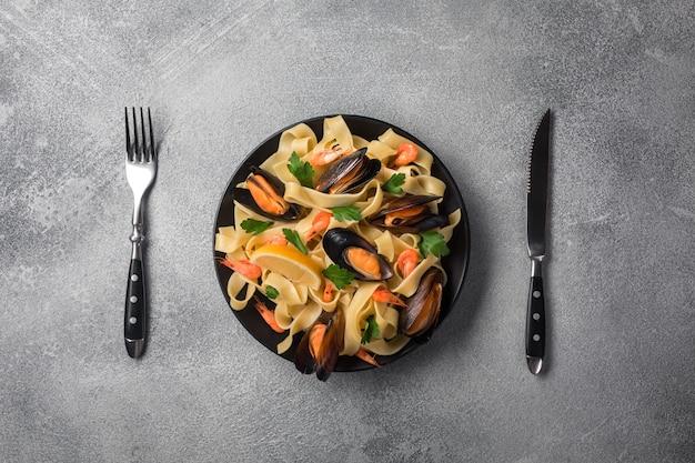 Tradycyjny Włoski Owoce Morza Makaron Z Małżami Spaghetti Alle Vongole Na Kamiennym Tle Z Garnelą I Małżami Premium Zdjęcia