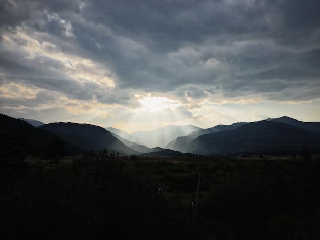 Trawiaste Pole Z Roślinami Z Górami I Słońcem świecącym Przez Chmury W Tle Darmowe Zdjęcia