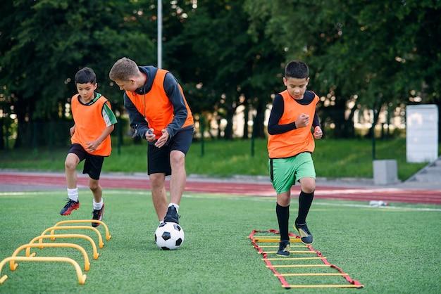 Trener Piłki Nożnej Obserwuje Swoich Podopiecznych Wykonujących ćwiczenia Biegowe Z Pokonywaniem Przeszkód Premium Zdjęcia