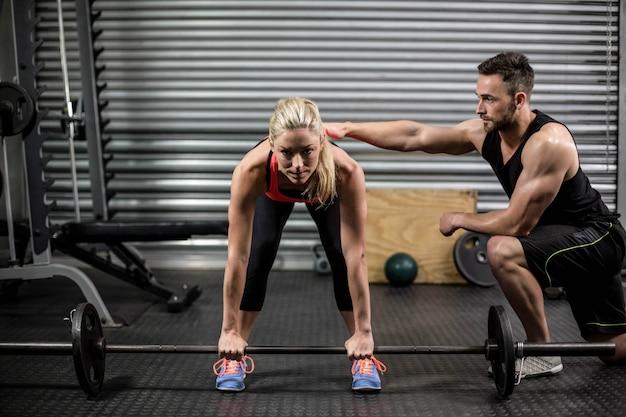 Trener Pomaga Kobieta Z Podnoszenia Brzana W Siłowni Premium Zdjęcia