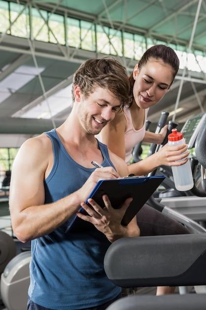 Trenera Writing Na Schowku Podczas Gdy Kobieta ćwiczy Na Eliptycznej Maszynie Premium Zdjęcia