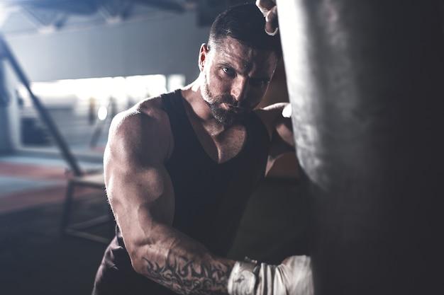Trening męskiego boksera z workiem treningowym w ciemnej hali sportowej. Premium Zdjęcia