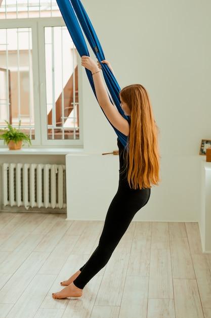 Trening Rozciągający. Zdrowy Tryb życia. Młoda Piękna Dziewczyna W Czarnym Mundurze Robi ćwiczenia Rozciągające. Akroyoga, Joga, Fitness, Trening, Sport. Premium Zdjęcia