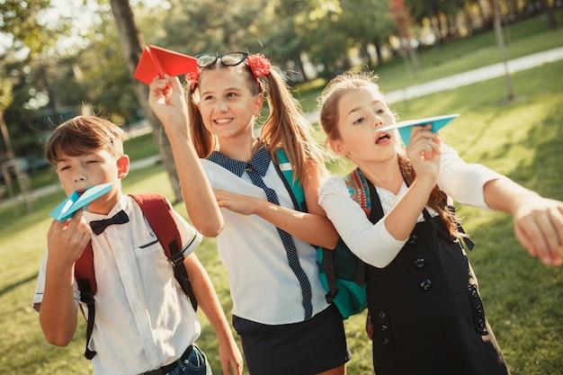 Troje Dzieci W Wieku Szkolnym Wystrzeliwuje Papierowe Samoloty W Niebo I Bawią Się W Parku Niedaleko Szkoły Premium Zdjęcia