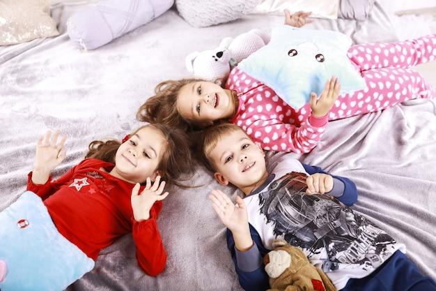 Troje Szczęśliwych Dzieci Leży Na Kocu Ubranym W Bielizna Nocną Darmowe Zdjęcia