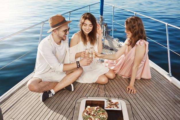 Troje Szczęśliwych I Wesołych Europejczyków Jedzących Obiad Na Jachcie, Pijących Szampana I Spędzających Razem Fantastyczny Czas. Przyjaciele Zorganizowali Przyjęcie Niespodziewane Na łodzi Dla Dziewczynki B-day Darmowe Zdjęcia