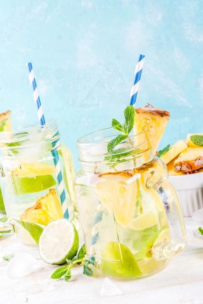 Tropikalny napój ananasowy mojito lub lemoniada ze świeżą limonką i miętą jasnoniebieskie tło Premium Zdjęcia