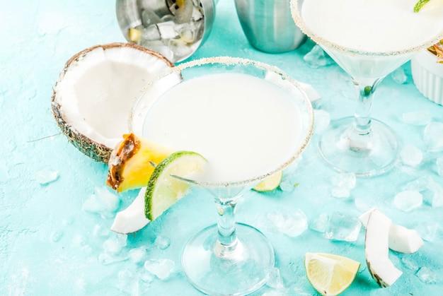 Tropikalny napój mrożony kokosowy ananasowy margaritas z mrożonym sokiem z ananasów tequili pina colada i limonką jasnoniebieskie tło Premium Zdjęcia