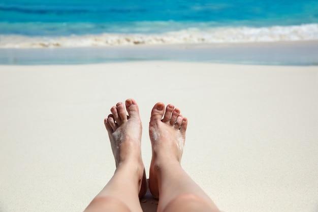 Tropikalny Tło. Stopa Na Plaży W Pobliżu Morza. Koncepcja Rekreacji Premium Zdjęcia