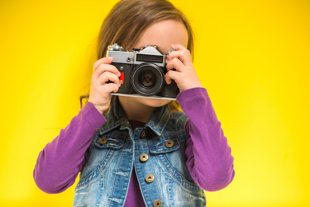 Troszkę śliczna dziewczyna robi fotografii na kolorze żółtym Premium Zdjęcia