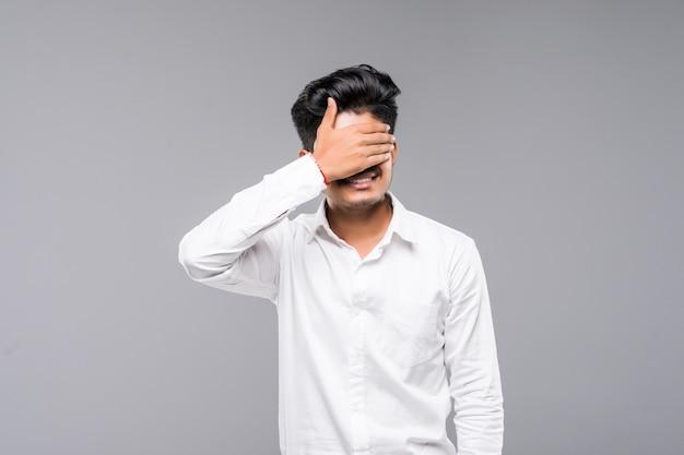 Trwanie Młody Indyjski Mężczyzna Zakrywa Jego Oczy Z Rękami, Odosobnionymi Na Białej ścianie. Darmowe Zdjęcia