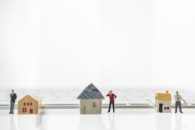 Trzech Biznesmenów Miniaturowa Postać Ludzi Stojących I Pracujących Z Domową Zabawką I Klawiaturą Komputerową. Premium Zdjęcia