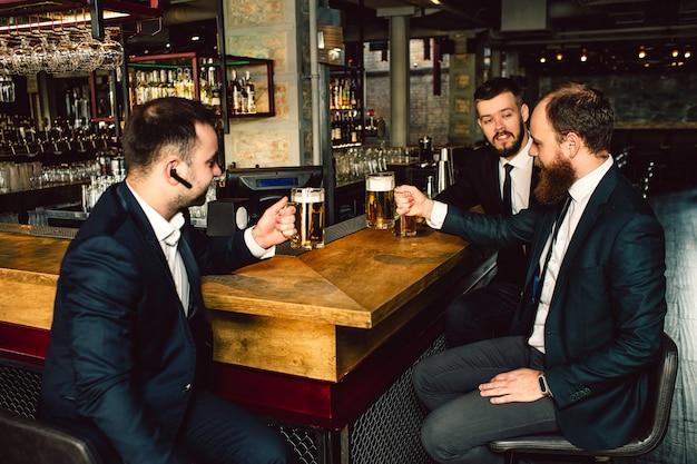 Trzech Młodych Biznesmenów Siedzieć Przy Stole I Trzymać łyki Piwa. Oni Rozmawiają. Ludzie Noszą Garnitury. Pierwszy Facet Ma Czarne Słuchawki W Uchu. Premium Zdjęcia