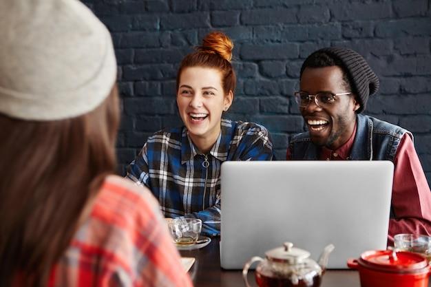 Trzech Szczęśliwych Entuzjastycznych Młodych Ludzi Przy Użyciu Komputera Przenośnego, Rozmawiając Przy Stole W Kawiarni. Międzynarodowy Zespół Omawiający Pomysły Biznesowe Podczas Lunchu. Darmowe Zdjęcia