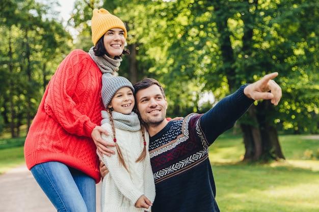Trzej członkowie rodziny spędzają razem czas, patrzą na piękne jezioro w parku, wskazują palcami Premium Zdjęcia
