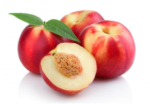 Trzy Dojrzałej Brzoskwini Owoc Z Plasterkami Odizolowywającymi Premium Zdjęcia