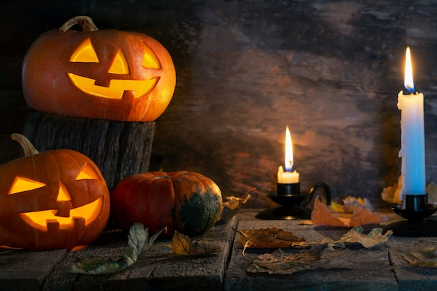 Trzy halloweenowej bani przewodzą jack o lampion na drewnianym stole Premium Zdjęcia