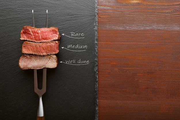 Trzy Kawałki Mięsa Na Widelcu Do Mięsa. Trzy Rodzaje Pieczenia Mięsa, Rzadkie, średnie, Dobrze Zrobione. Premium Zdjęcia