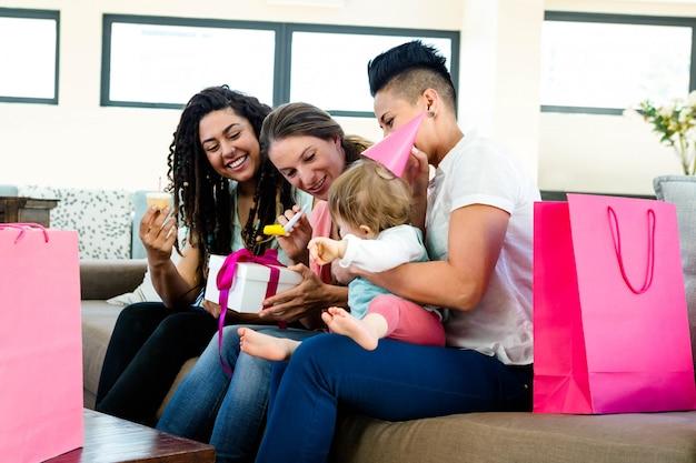 Trzy kobiety siedzące na kanapie z okazji pierwszych urodzin dziecka Premium Zdjęcia