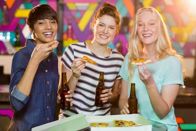 Trzy Koleżanki Posiadające Butelkę Piwa I Pizzy W Partii Premium Zdjęcia
