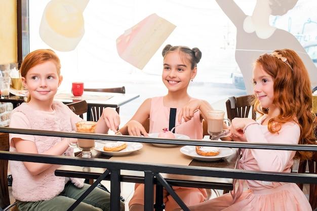 Trzy Małe Dziewczynki Siedzące Przy Stoliku W Kawiarni Radośnie Piją Gorącą Czekoladę I Jedzą Ciasta Premium Zdjęcia
