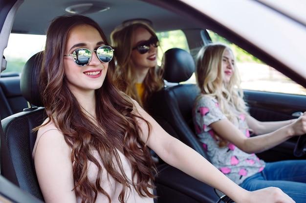 Trzy młode dziewczyny podróżujące samochodem Premium Zdjęcia