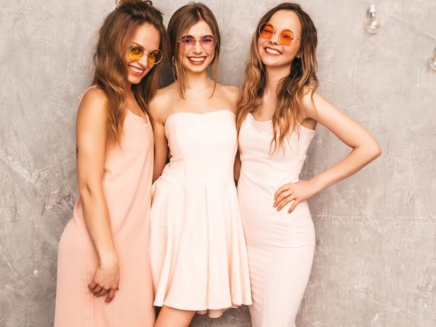 Trzy Młode Piękne Uśmiechnięte Dziewczyny W Modnych Letnich Jasnoróżowych Sukienkach. Seksowny Beztroski Kobiet Pozować. Pozytywne Modele W Okrągłych Okularach Przeciwsłonecznych świetnie Się Bawią Darmowe Zdjęcia