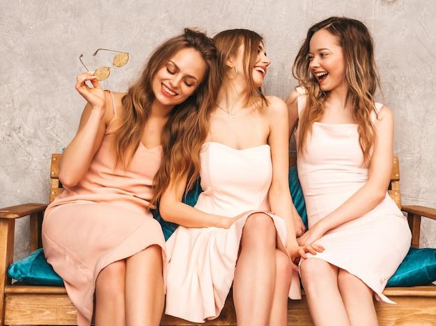 Trzy Młode Piękne Uśmiechnięte Dziewczyny W Modnych Letnich Różowych Sukienkach. Seksowne Beztroskie Kobiety Siedzi Na Kanapie W Luksusowym Wnętrzu. Pozytywne Modele W Okrągłych Okularach Przeciwsłonecznych świetnie Się Bawią I Komunikują Darmowe Zdjęcia
