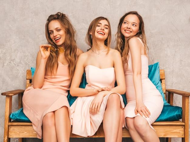 Trzy Młode Piękne Uśmiechnięte Dziewczyny W Modnych Letnich Różowych Sukienkach. Seksowne Beztroskie Kobiety Siedzi Na Kanapie W Luksusowym Wnętrzu. Pozytywne Modele Zabawy I Komunikacji Darmowe Zdjęcia