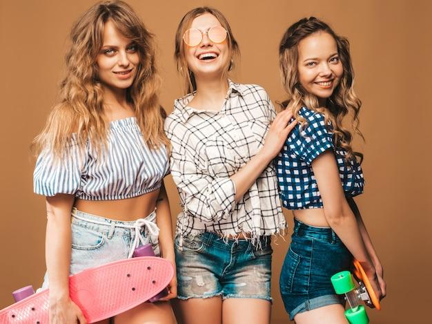 Trzy Młode Stylowe Seksowne Uśmiechnięte Piękne Dziewczyny Z Kolorowymi Deskorolkami Grosza. Kobiety W Letnie Ubrania W Kraciaste Koszule Pozowanie W Okulary Przeciwsłoneczne. Pozytywne Modele Zabawy Darmowe Zdjęcia