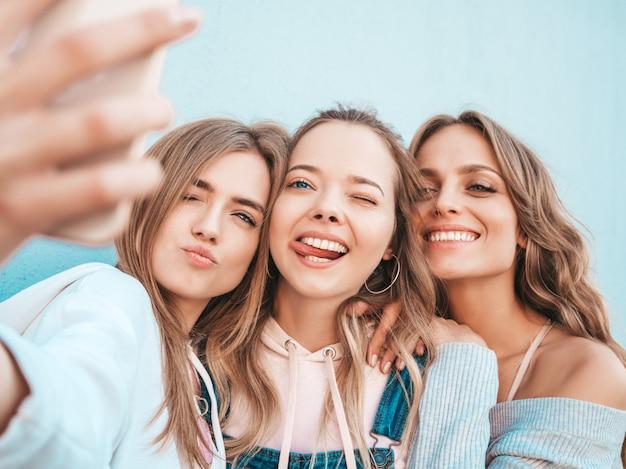 Trzy Młode Uśmiechnięte Kobiety Hipster W Letnie Ubrania. Dziewczyny Biorące Selfie Autoportret Zdjęcia Na Smartfonie. Modele Pozowanie Na Ulicy W Pobliżu ściany. Kobieta Pokazująca Pozytywne Emocje Na Twarzy. Pokazujący Język Darmowe Zdjęcia