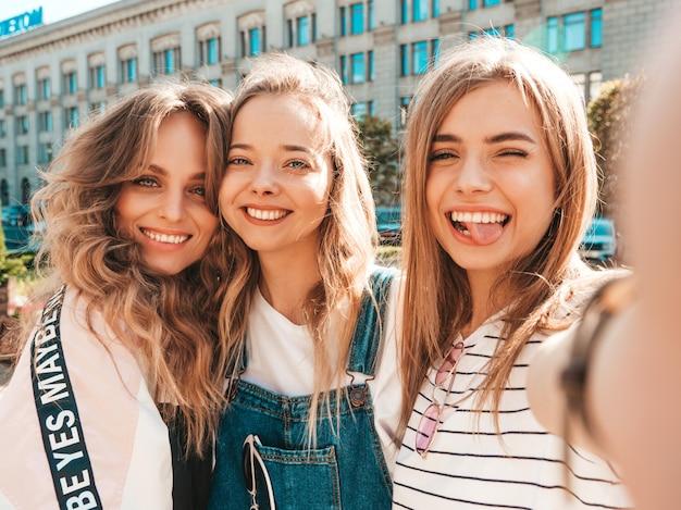 Trzy Młode Uśmiechnięte Kobiety Hipster W Letnie Ubrania. Dziewczyny Robienia Zdjęć Autoportretów Na Smartfonie. Modele Pozowanie Na Ulicy. Kobieta Pokazująca Pozytywne Emocje Na Twarzy Darmowe Zdjęcia