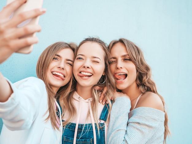 Trzy Młode Uśmiechnięte Kobiety Hipster W Letnie Ubrania. Dziewczyny Robienia Zdjęć Autoportretów Na Smartfonie. Modele Pozowanie Na Ulicy W Pobliżu ściany. Kobieta Z Pozytywnymi Emocjami Twarzy Darmowe Zdjęcia