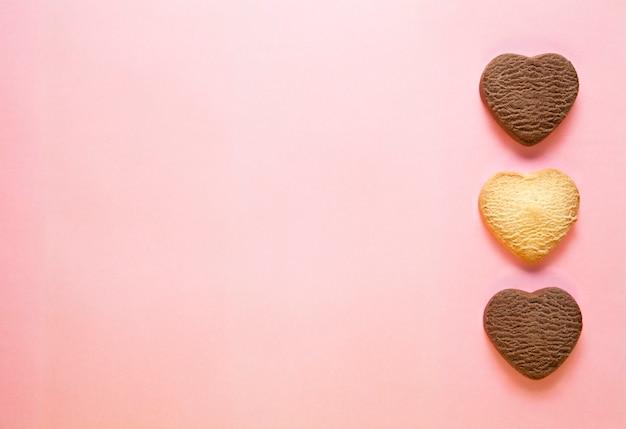 Trzy Pieczone Ciasteczka W Kształcie Serca Na Różowym Tle. Premium Zdjęcia