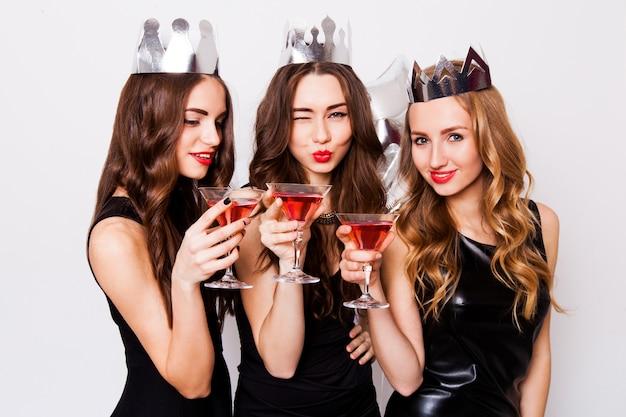 Trzy Piękne Eleganckie Kobiety świętują Wieczór Panieński I Piją Koktajle. Najlepsi Przyjaciele W Czarnej Sukience Wieczorowej, Koronie Na Głowie I Brzęczących Okularach. Jasny Makijaż, Czerwone Usta. Wewnątrz. Darmowe Zdjęcia
