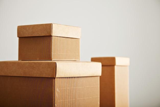 Trzy Podobne Beżowe Pudełka Z Tektury Falistej Z Okładkami O Różnych Kształtach I Rozmiarach Na Białym Tle Darmowe Zdjęcia