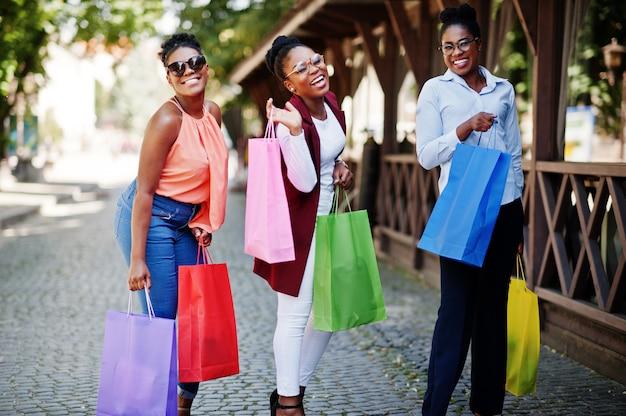 Trzy Przypadkowe Dziewczyny Afroamerykanów Z Kolorowe Torby Na Zakupy Spacery Na świeżym Powietrzu. Stylowe Czarne Zakupy Kobiet. Premium Zdjęcia