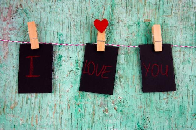 Trzy Puste Etykiety Z Napisem Kocham Cię I Czerwone Serce Na Szpilkach Tkaniny Wiszące Na Linie Premium Zdjęcia