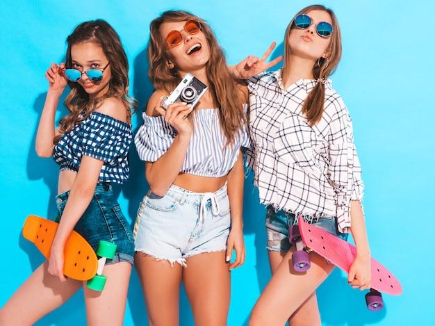 Trzy Seksowne Piękne Stylowe Uśmiechnięte Dziewczyny Z Kolorowymi Deskorolkami Grosza. Kobiety W Lecie Pozowanie Ubrania Kraciaste Koszule. Modele Robiące Zdjęcia Aparatem Fotograficznym Retro Darmowe Zdjęcia