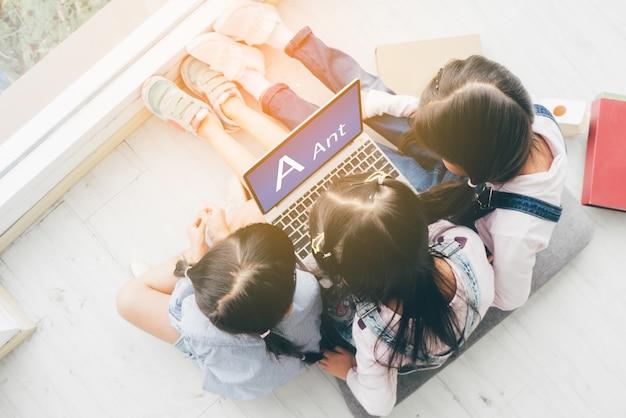 Trzy siostry, leżą na podłodze i używają laptopa do pracy szkolnej. Premium Zdjęcia