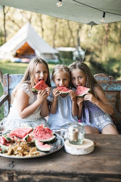 Trzy śliczne Szczęśliwe Uśmiechnięte Dziewczyny, Siostry, Diabły, Siedzący Przy Stole Na Vintage Drewnianej ławce I Jedzenie Arbuza Na Zewnątrz Premium Zdjęcia