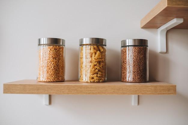 Trzy Słoiki Z Makaronem, Bulgur, Kaszą Gryczaną Na Półce Jako Zdrową żywność Premium Zdjęcia