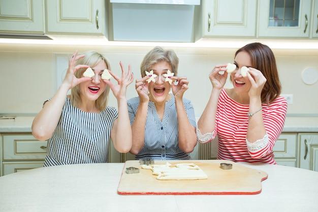 Trzy Stylowe Dorosłe Kobiety Robiące Ciasteczka W Kuchni Premium Zdjęcia