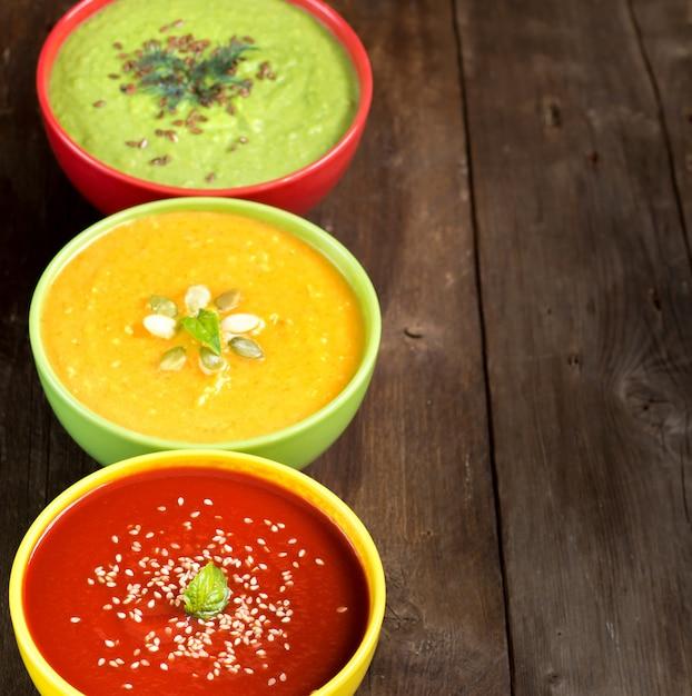 Trzy świeże Kolorowe Zupy Warzywne - Pomidor, Dynia I Zielony Groszek Na Drewnianym Stole Premium Zdjęcia