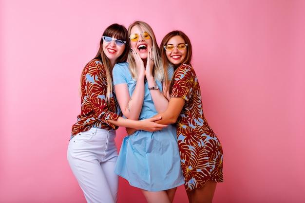 Trzy Szczęśliwe Młode ładne Kobiety Robiące Selfie, Grupa Najlepszych Przyjaciół, Bawiąca Się, Stylowe Modne Tropikalne Nadruki Dopasowane Kolorystycznie Ubrania I Okulary Vintage, Różowa ściana. Darmowe Zdjęcia